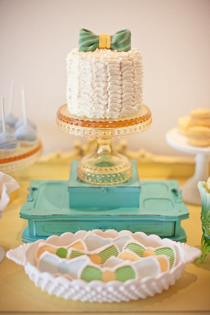 various bow-tie colored cookies with ivory ruffle cake topped with large bow tie