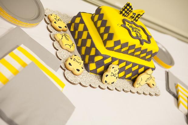 A delightful yellow and gray Little Man themed baby shower cake