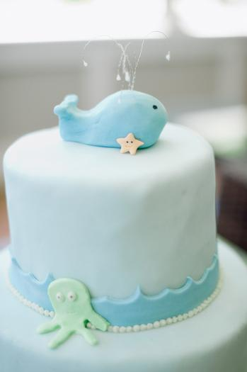 under the sea baby shower ideas, blue colored hydrangeas, baby onesies clothesline creatures whale, cake with whale, octopus, starfish