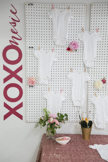 Sweet XOXO Baby Shower, backdrop with onesies hanging