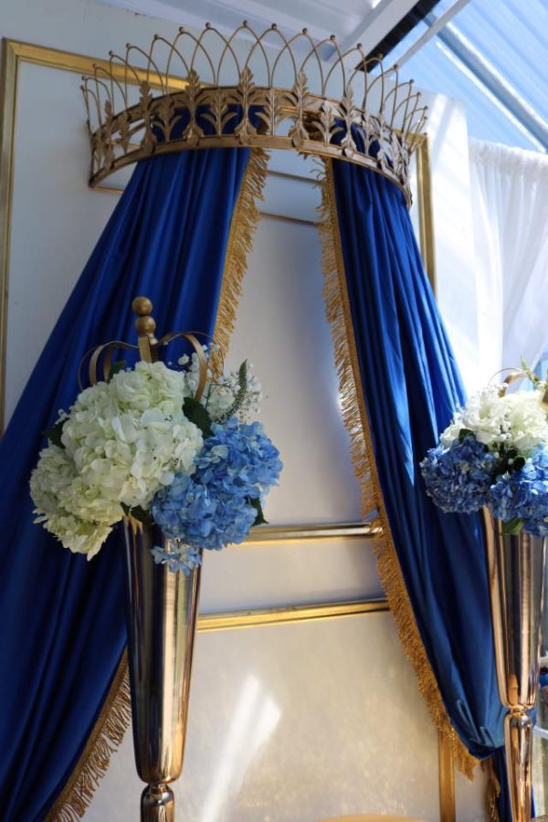 large gold crown with royal blue curtains